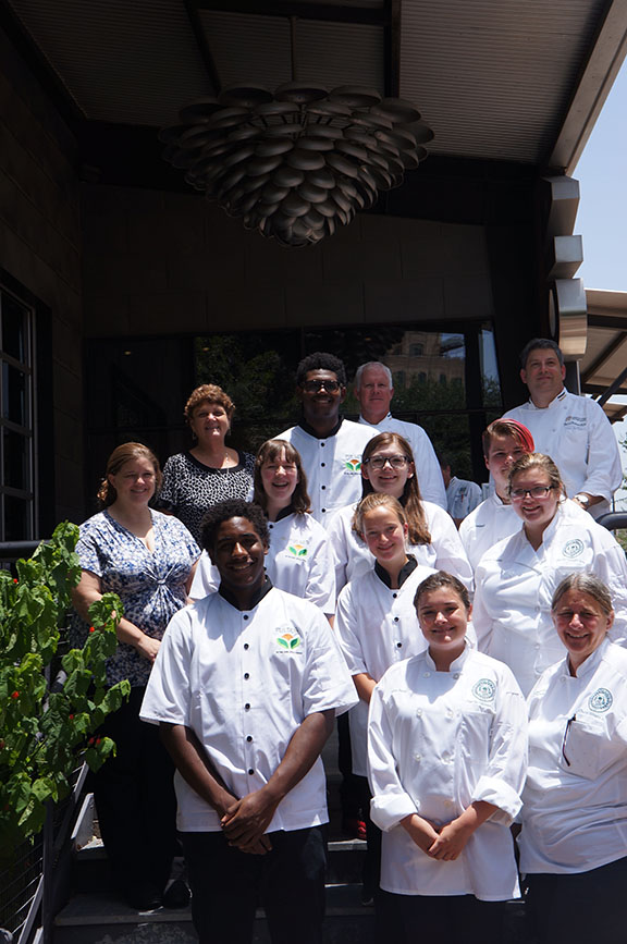Contestants posing for a photo wearing Pulses chef aprons.